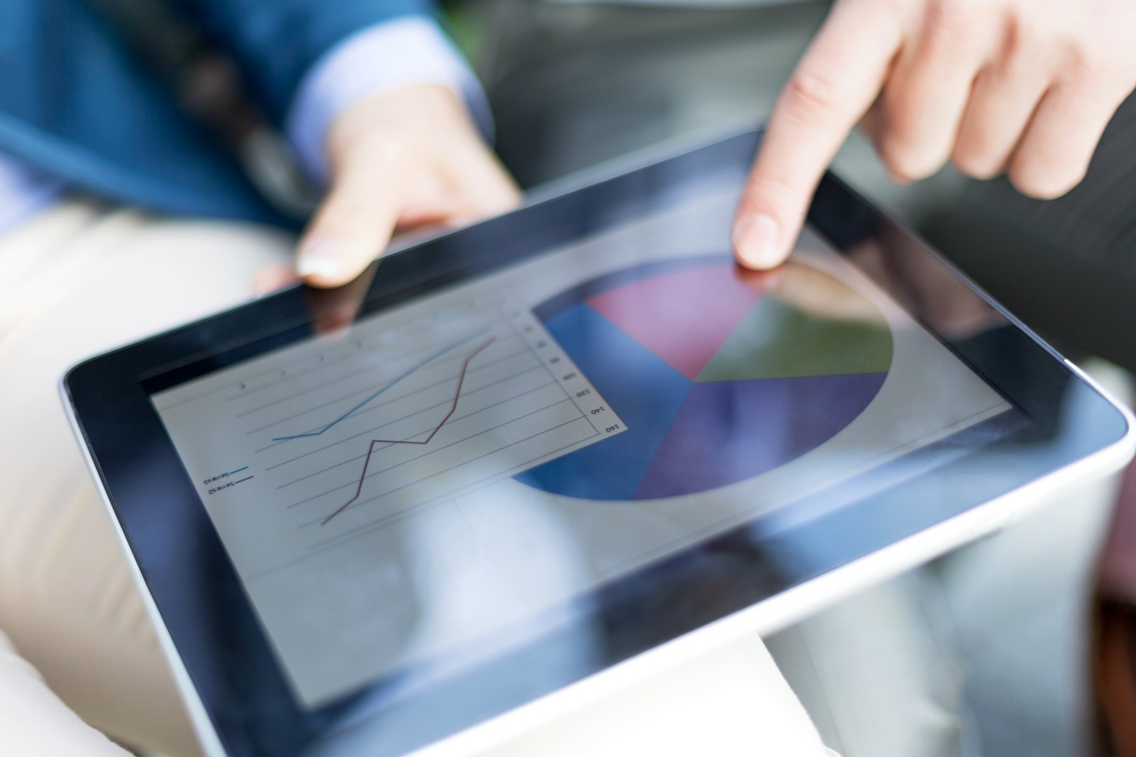 Business people examining graph and chart on digital tablet